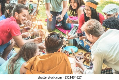Happy friends making picnic dinner on city park outdoor - Young trendy people drinking wine and laughing outside - Focus on left man face - Youth, food, summer lifestyle and friendship concept