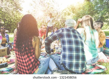 Happy friends making picnic dinner on city park outdoor - Young trendy people drinking wine and laughing outside - Focus on center guys faces - Youth, food, summer lifestyle and friendship concept