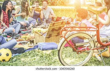 Happy friends making picnic on pubblic park outdoor - Young trendy people drinking wine and laughing in nature - Focus on man with hat and two girls next him - Youth and friendship concept