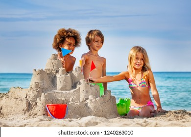 Happy friends making sandcastle on the beach