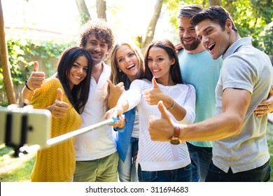 Happy friends making selfie photo on smartphone while showing thumbs up outdoors