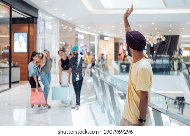 Happy friends meeting and greeting ina shopping mall. Unrecognizable man waving to group of friends he meet in the shopping mall