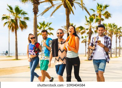 Happy friends on seaside walk in Barcelona. Multiracial group of best friends enjoying summer and time together. Happiness and friendship during a travel in Spain