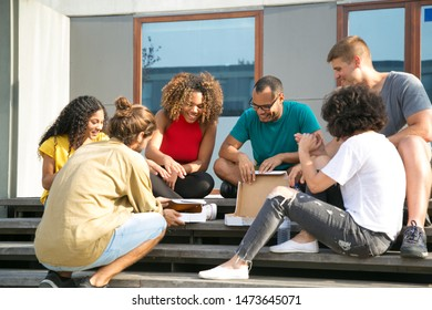 Happy friends opening boxes with pizza. Mix raced group of young people sitting on outdoor stairs and enjoying takeaway meal. Fast food outdoors concept