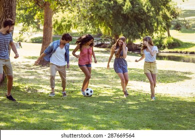 Happy friends in the park with football on a sunny day