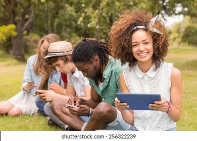 Happy friends in the park looking at tablet on a sunny day