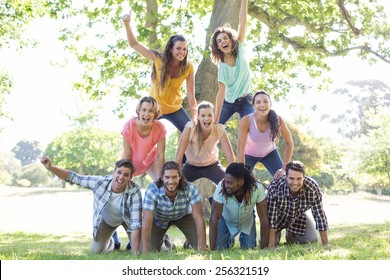 Happy friends in the park making human pyramid on a sunny day