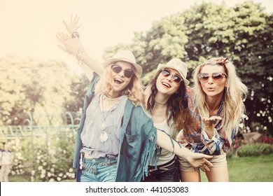 Happy friends in the park on a sunny day . Summer lifestyle portrait of three hipster women  enjoy nice day, wearing bright sunglasses. Best friends girls having fun, joy. Lifestyle