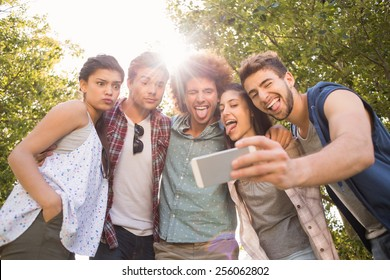 Happy friends in the park taking selfie on a sunny day