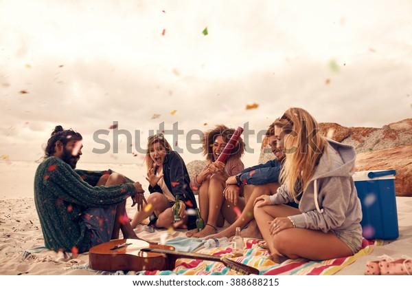 Fröhliche Freunde, die am Strand mit Getränken und Konfetti feiern. Fröhliche junge Leute, die sich auf der Strandparty amüsieren und mit Konfetti feiern.