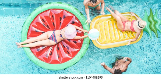 Happy friends playing with air lilo ball inside swimming pool - Young people having fun on summer vacation - Travel, holidays, youth lifestyle, friendship and tropical concept