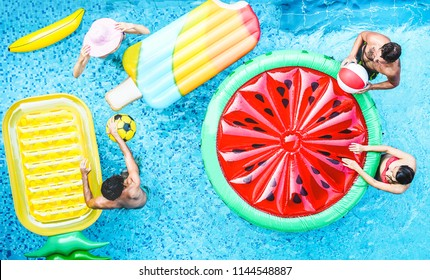 Happy friends playing with air lilo ball inside swimming pool - Young people having fun on summer holidays vacation - Travel, generation trends youth lifestyle, friendship and tropical concept