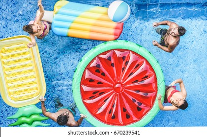 Happy friends playing with ball inside swimming pool - Young people having fun on summer holidays vacation - Travel,holidays,youth,friendship and tropical concept - Seasonal color tones filter