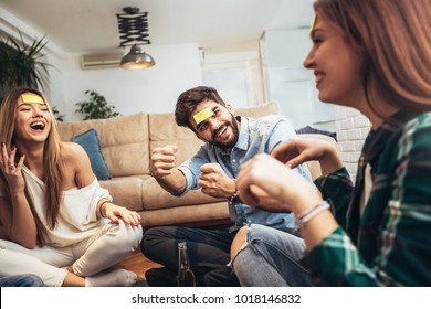 Happy friends playing game guess who and having fun at home