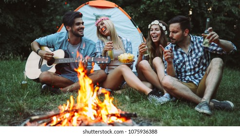 Happy friends playing music and enjoying bonfire