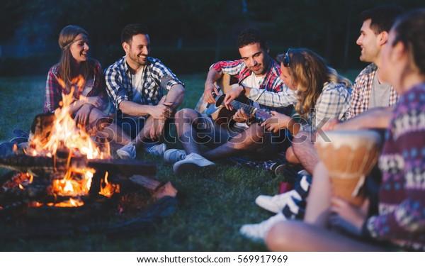 Glückliche Freunde spielen Musik und genießen das Feuer in der Natur