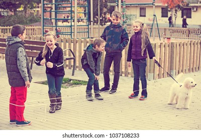 Happy  friends  playing rubber band jumping game and laughing outdoors