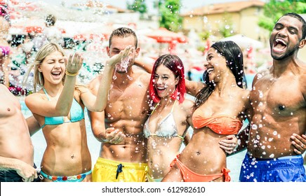 Happy friends playing in swimming pool party - Young diverse culture people having fun on summer vacation - Main focus on center guys - Youth and friendship concept - Warm contrast filter