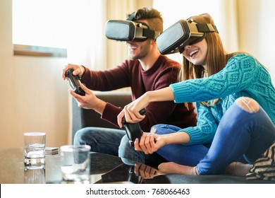 Happy friends playing video games wearing virtual reality glasses in their apartament - Young people having fun with new trends technology - Gaming concept - Focus on woman front headset