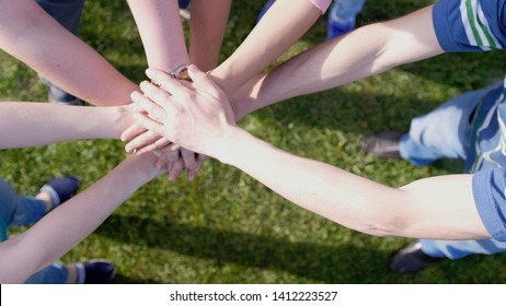 Happy friends putting their hands on top of each other on the grass on the background symbolizing unity and teamwork.