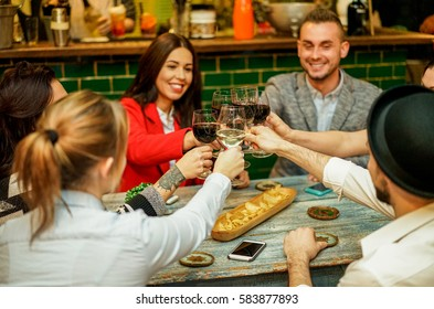 Happy friends raising glasses for cheering and toasting wine in trendy cocktail bar restaurant - Young people enjoying appetizer before dinner - Focus on women left hands - Unfiltered photo with flash