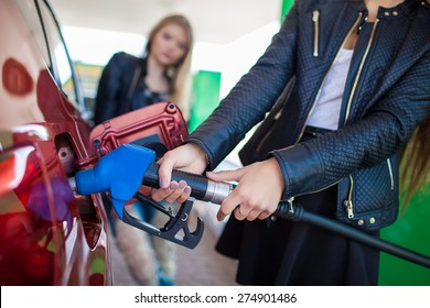 Happy friends refuel car in gas station. Holiday trip of friends