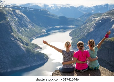 Happy friends relax on Trolltunga. People enjoy beautiful lake and good weather in Norway.