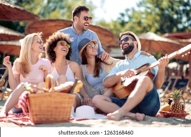 Happy friends relaxing and playing guitar on the beach.Having fun at beach party.