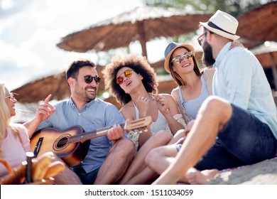 Happy friends relaxing and playing guitar at the beach.Having fun at beach party .