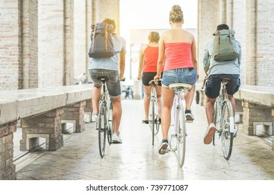 Happy friends riding city bikes in old town center - Young students having fun together going around with bicycles - Youth, friendship and lifestyle concept - Focus on right woman body