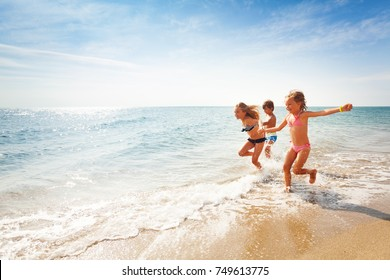 Happy friends running along edge of sea in summer