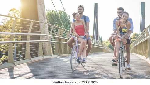 Happy friends running bicycles on bridge city park - Young people having fun in sunny day - Youth, friendship and healthy lifestyle concept - Main focus on left couple - War filter