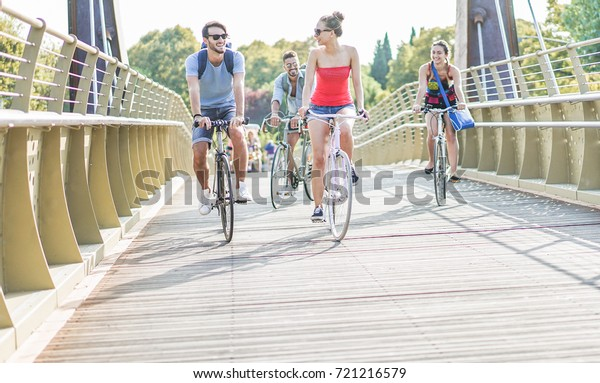 Happy friends running bicycles on bridge city park - Young people having fun after university going back at home - Youth, friendship and healthy lifestyle concept - Main focus on left girl