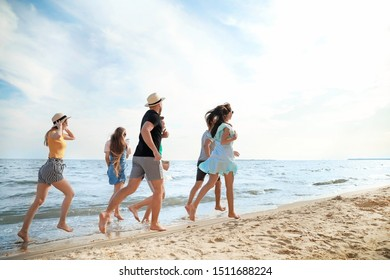 Happy friends running on sea beach at resort