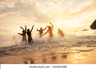 Happy friends runs or having fun at idyllic sunset sea
