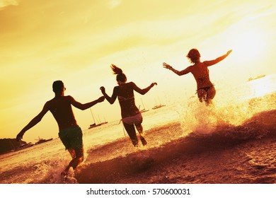 Happy friends runs to the sea. Friendship travel concept at sunset time