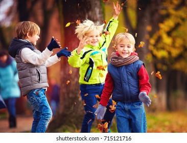 happy friends, schoolchildren having fun in autumn park among fallen leaves