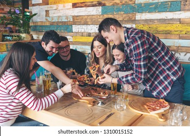 Happy friends sharing pizza at restaurant - Friendship concept with young people enjoying time together and having genuine fun at rustic pizzeria eating pizza - Focus on guy with glasses