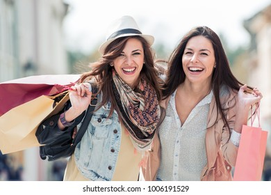 Happy friends shopping.Two beautiful young women enjoying shopping in the city.