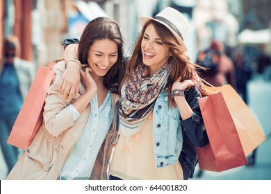 Happy friends shopping. Two beautiful young women enjoying shopping in the city.