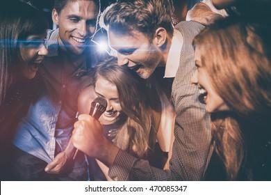 Happy friends singing karaoke together at the nightclub