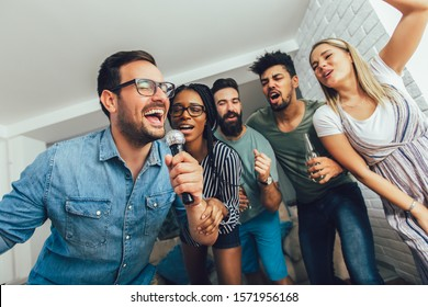Happy friends singing together at home. Karaoke party concept