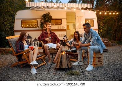 Happy friends sitting near campfire in the evenin