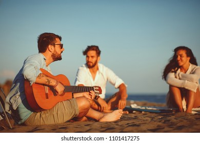 Happy friends sitting on the beach singing and playing guitar