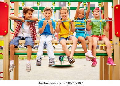 Happy friends sitting on swing and looking at camera