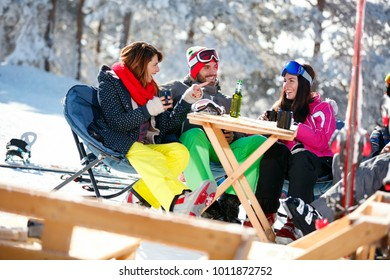 Happy friends spending time together and drink after skiing in cafe at ski resort in mountains