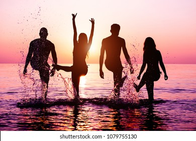 Happy friends splashing water on tropical beach at sunset - Group of young people having fun on summer vacation - Youth lifestyle, party and friendship concept - Focus on bodies silhouette