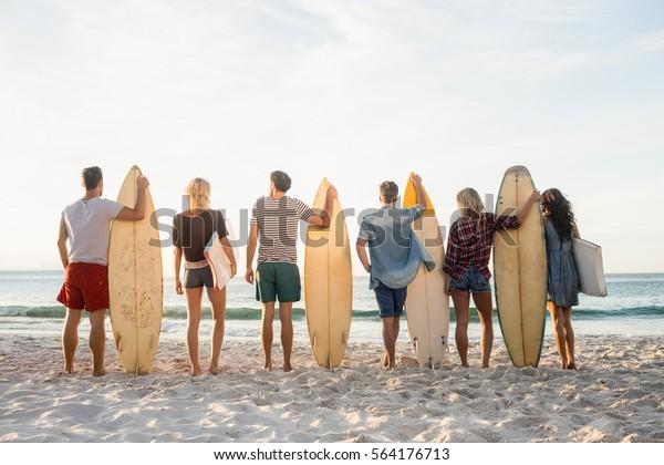 Glückliche Freunde, die sich mit Surfbrettern am Strand in Einklang stehen