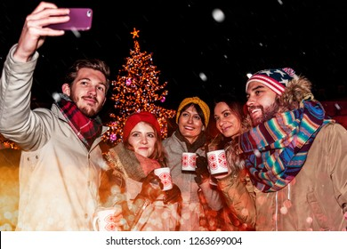 happy friends take a selfie on a christmas market besides a huge christmas tree with colourful decoration. captured through glittering bengal light sparkles while snowing. focus on woman in the middle