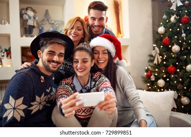 happy friends taking photo with mobile phone for Christmas